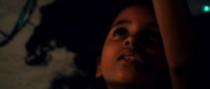Sophia deitada no chão sentindo as vibrações que saem de uma caixa de aparelho de som.