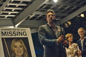Nick (Ben Affleck) discursando para a população de sua comunidade sobre as acusações de assassinato que começaram a ser feitas.