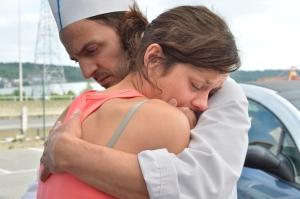 Sandra (Cotillard) consolada por seu marido Manu (Rongione) enquanto tenta se segurar em pé diante da sua complicada situação.